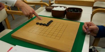 """テキストと進行表入りのマイファイルをもらい、レッツレッスン! 勝負は""""地(じ)""""と呼ばれる陣地の多い方が勝つ、線と線の交点に石を置くなど囲碁のマナーとルールを理解。(イメージ)"""