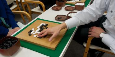 陣地数えやすくするために石を整理する「整地」は重要。テキストで1時間勉強の後は、いよいよ対局に。インストラクターの指導を受けつつ打ち、最後に整地をして勝敗を確認。この体験で一気に囲碁に親しみが湧いた。(イメージ)